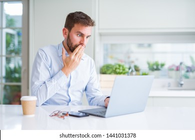 Handsome man working using computer laptop and drinking a cup of coffee cover mouth with hand shocked with shame for mistake, expression of fear, scared in silence, secret concept