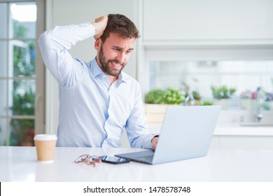 Handsome man working using computer laptop and drinking a cup of coffee stressed with hand on head, shocked with shame and surprise face, angry and frustrated. Fear and upset for mistake.