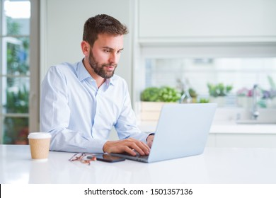 Handsome man working using computer laptop and drinking a cup of coffee with a confident expression on smart face thinking serious