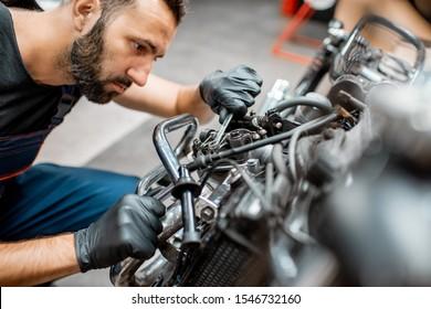 Handsome man in workwear adjusting engine valves of a beautiful vintage motorcycle at the workshop