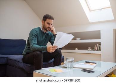 Handsome man worried about unpaid bills at home.