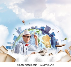 Handsome man writer in hat and eyeglasses pointing up while using typing machine at the table with flying books and Earth globe among cloudy skyscape on background. Elements of this image furnished by