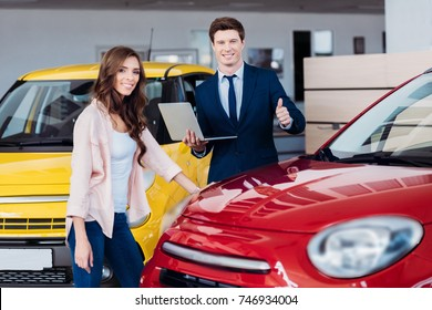 Handsome manager showing thumb up to car while standing near customer