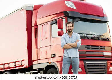 handsome masculine truck driver standing outside with his vehicle behind with folded arms