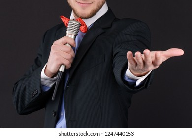 Handsome Master of ceremonies in black suit holding microphone in hand on black background. Showman, tv. closeup