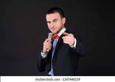 Handsome Master of ceremonies in black suit holding microphone in hand on black background. Showman, tv