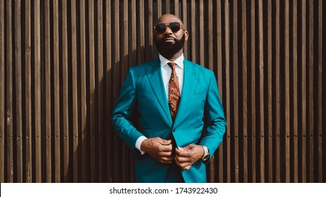 A handsome mature bald bearded African man in a sunglasses and a fashionable blue or teal costume with a tie is standing in front of a wall made of striped wooden timbers and fastening a suit button