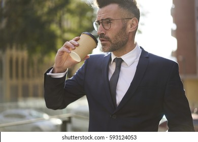 Handsome mature bearded male project manager enjoying hot coffee outdoors during work break preparing for attending business meeting thinking over reporting about creative strategy for startup