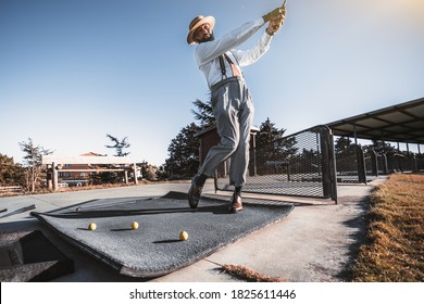 A handsome mature bearded retrosexual black guy in trousers with suspenders, white shirt, and hat is got the stance and hit the ball with a golf club on a golf field; several yellow balls near him