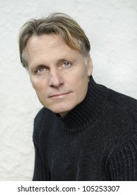 handsome mature blond man in his forties wearing a black sweater.