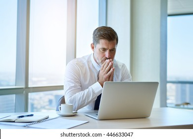 Handsome and mature business executive sitting at his desk in a modern office with large windows looking seriously at information on the screen of his laptop computer