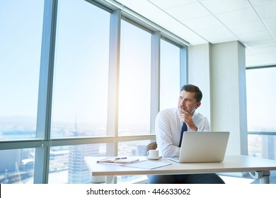 Handsome mature business leader sitting in a modern office with large windows, at his tidy desk with laptop open, looking out through the window with a positive expression and gentle sunflare