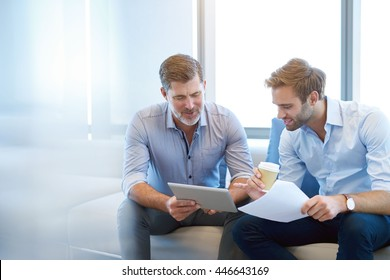 Handsome mature business manager using a digital tablet to discuss something positive with a young employee in a modern business lounge