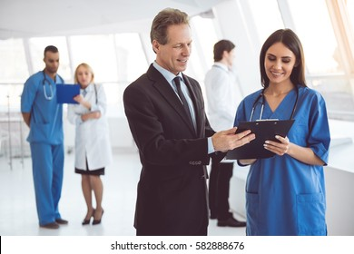 Handsome mature businessman and beautiful young doctor are discussing documents and smiling while standing in the hospital hall