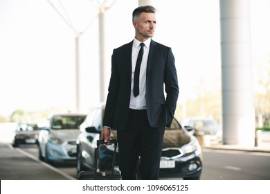 Handsome mature businessman catching a taxi while walking outside the airport with a suitcase