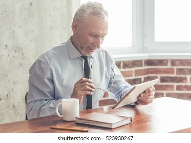Handsome mature businessman in formal suit is using a digital tablet, holding glasses and smiling while working in office