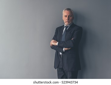 Handsome mature businessman in formal suit is looking at camera while standing with crossed arms on gray background