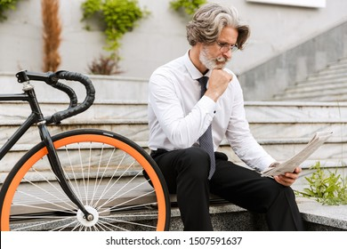 Handsome mature businessman in formalwear sitting on a bench outdoors, reading newspaper