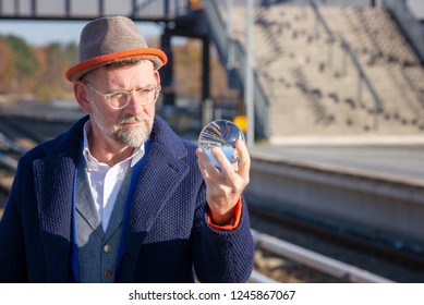 handsome mature businessman looking at glass sphere at train station