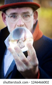 handsome mature businessman looking at a glass sphere