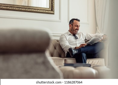 Handsome mature businessman reading a magazine while relaxing in hotel room. Man on business trip staying in a hotel.