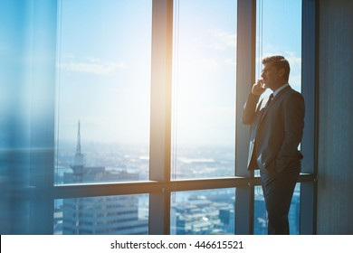 Handsome mature businessman standing in a professional corporate suit alongside large windows with a view of the city, talking on his mobile phone and looking out