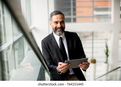 Handsome mature businessman with tablet in the office