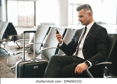 Handsome mature businessman using mobile phone while sitting at the airport lobby with a suitcase