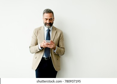 Handsome mature businessman using mobile phone in the office
