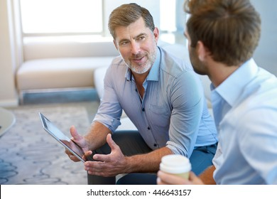 Handsome and mature corporate leader sitting in a business lounge with a young man, offering mentoring advice to him while holding a digital tablet
