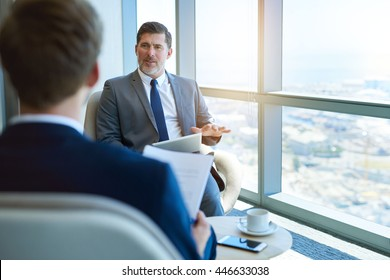 Handsome mature corporate manager sitting in a modern office space, holding a digital tablet while interviewing a young business applicant