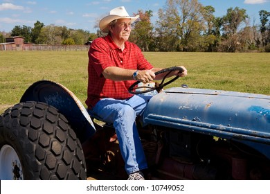 Handsome mature cowboy riding his tractor through his fields.