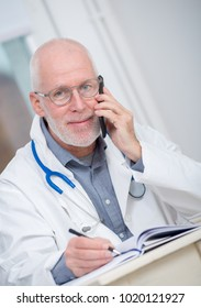 handsome mature doctor on phone at his office