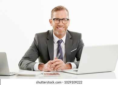 Handsome mature financial director businessman looking at camera and smiling while sitting at desk in front of laptops and working online. Isolated on white background.