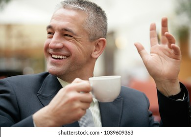 Handsome mature gray-haired businessman wearing a suit drinking cup of coffee sitting in restaurant and say hello, hi, welcome