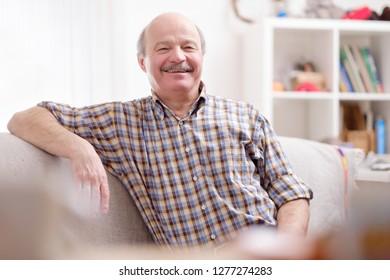Handsome mature hispanic man sitting on sofa