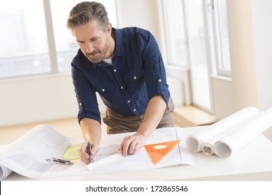 Handsome mature male architect working on blueprint at office desk