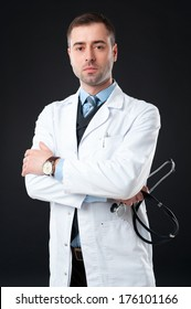 Handsome mature male doctor with stethoscope in hand on black or dark grey background. Classic style in waistcoat with blue shirt and tie