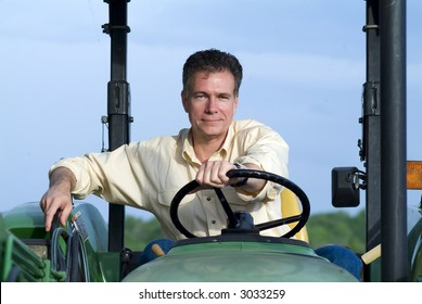 Handsome mature male sitting comfortably on a big green tractor smiling confidently.