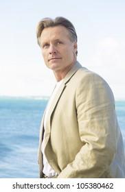 handsome mature man in beige blazer standing by the sea