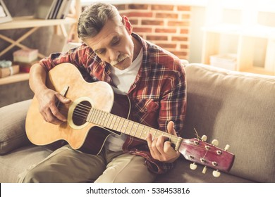 Handsome mature man in casual clothes is smiling while playing guitar at home
