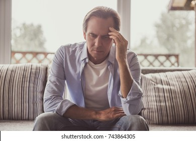 Handsome mature man in casual clothes is sitting sad on couch at home