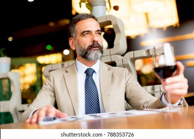 Handsome mature man drinking red wine during lunch