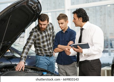 Handsome mature man and his teenage son choosing a new car at the dealership talking to a professional salesman checking out engine of a car with a n open hood automotive cars sales vehicle transport