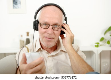 handsome mature man listening to music with headphones at home