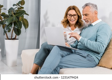 handsome mature man pointing by hand at laptop screen to beautiful wife on sofa at home