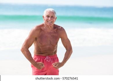 Handsome mature man showing his muscles on the beach