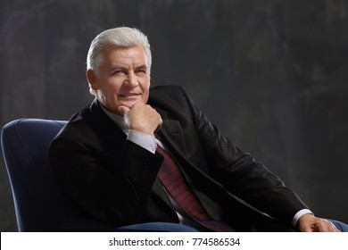 Handsome mature man sitting in armchair on dark background