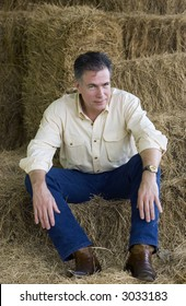 Handsome mature man sitting on some bales of hay at the end of an afternoon of working with the horses.