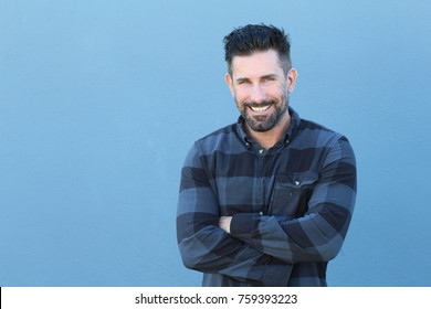 Handsome mature man smiling and laughing while crossing his arms with copy space